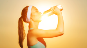 Woman drinking water in sun, detoxing